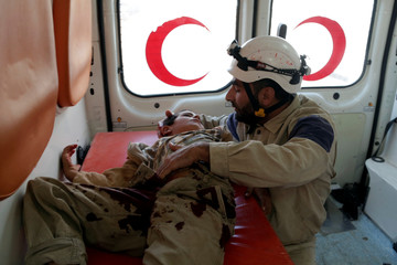 A civil defence member holds an injured boy inside an ambulance after what activists said were cluster bombs dropped by Russian air force in Maaret al-Naaman town in Idlib province