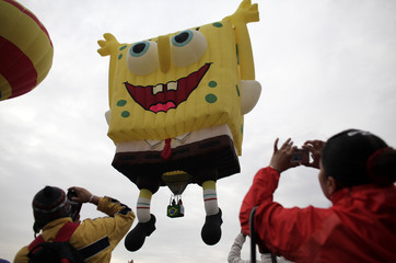 Visitors take pictures of a hot-air balloon in the shape of SpongeBob SquarePants during the 12th International Hot-Air Balloon Festival at the Metropolitano park in Leon
