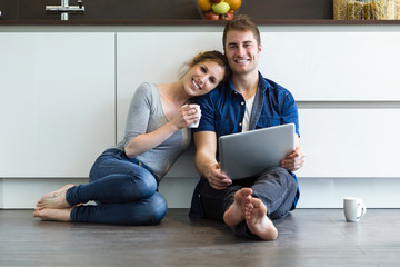 Beautiful young couple using they digital tablet in the kitchen at home.