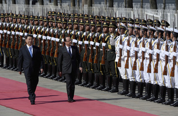 Chinese President Xi Jinping escorts French President Francois Hollande as they review an honour guard outside the Great Hall of the People in Beijing
