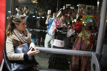 Israelis dressed as zombies look through a window at a bus station as they take part in an annual Zombie Walk procession for the Jewish holiday of Purim in Tel Aviv