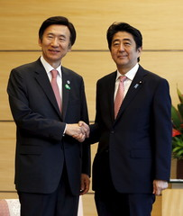 South Korea's Foreign Minister Yun Byung-se shakes hands with Japan's Prime Minister Shinzo Abe at the start of their talks at Abe's official residence in Tokyo