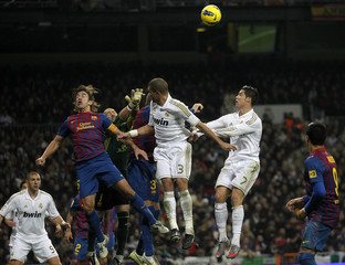 "Barcelona's Puyol, Valdes and Pique jumps for the ball against Real Madrid during their Spanish first division soccer match, the ""Clasico"",  at the Santiago Bernabeu stadium in Madrid,"