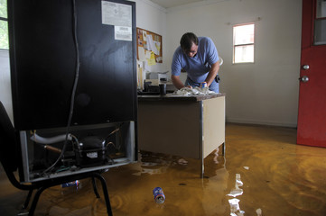 Tony Kiriwas leaves a note in the flooded office of his auto sales shop as floodwater associated with Tropical Storm Debby rises around him in New Port Richey