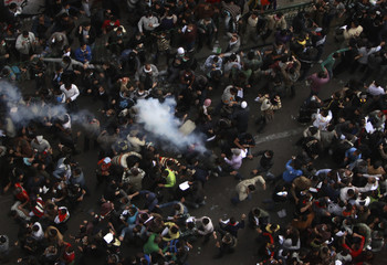 Protesters run from tear gas fired by riot police during clashes near Tahrir Square