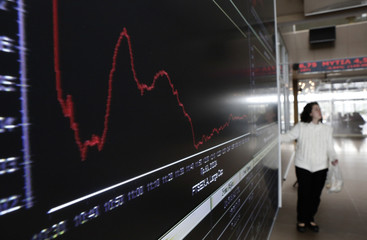 A woman stands next to an electronic board at the reception hall of the Athens stock exchange