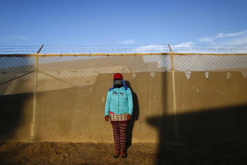 A farmworker poses for a photo with a handkerchief tied around her face to shield her against the sun and pesticide sprayed on fruits and vegetables in the farms, at Las casitas neighborhood in San Quintin in Baja California state