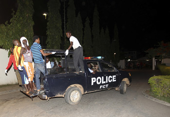 Volunteer rescue workers travel on a police van used to evacuate victims after a bombing to Asokoro General Hospital in Abuja