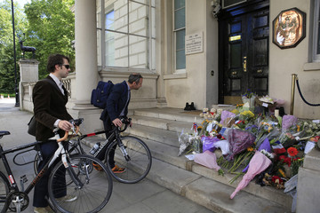 People look at floral tributes in memory of the Bastille Day truck attack in Nice left at the French embassy in London