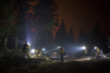 Members of El Carrizo Hot Shots crew cut fire a line through the night to try to contain the Lake Fire in the San Bernardino National Forest, California