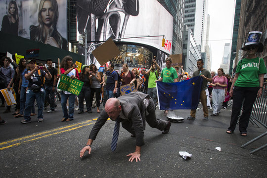 Performance artist John Bonafede marches on his hands as he drags dry ice, in representation of  glaciers, while taking part in the People's Climate March through Times Square, New York