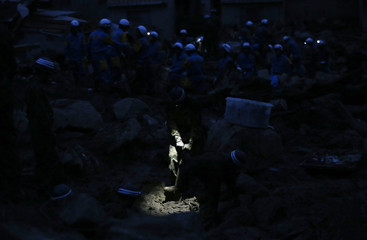 JSDF soldier searches for survivors at dusk at a site where a landslide swept through a residential area at Asaminami ward in Hiroshima