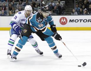 Canucks left wing Higgins and Sharks defender Burns battle for the puck during NHL game in San Jose