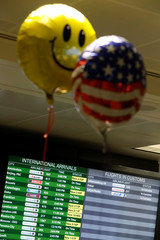 A balloon with a smiley-face and another with a U.S. flag pattern float in the international arrivals area as families affected by the recent travel ban are reunited at Washington Dulles International Airport in Chantilly, Virginia
