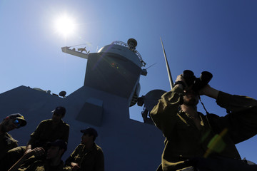 An Israeli soldier use his binoculars on an Israeli Navy vessel in the Mediterranean sea