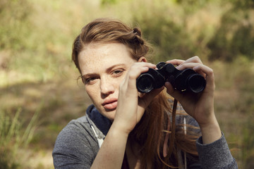 Portrait of young woman with binoculars