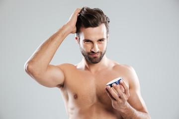 Obraz Man straighten hair and holding cream isolated - fototapety do salonu