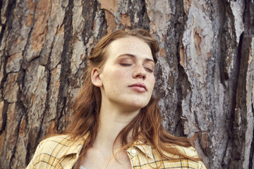 Portrait of redheaded young woman leaning against tree trunk with eyes closed