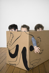 Three boys inside a cardboard box painted with an octopus