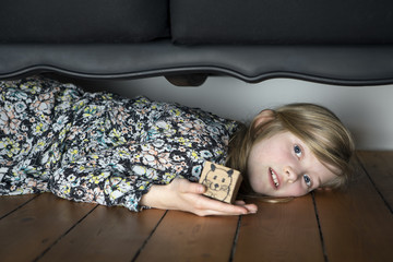 Girl lying on floor holding box with painted mouse