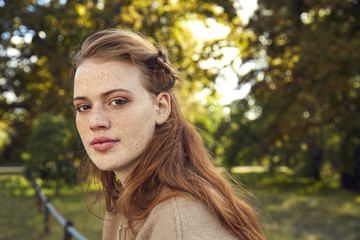 Portrait of redheaded young woman with freckles in a park