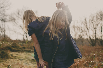 Two sisters dancing on a meadow