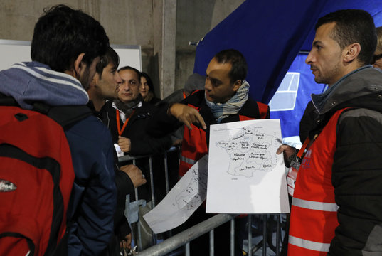 Migrants look at a map of France at a processing centre to be registered on the second day of their evacuation and transfer to reception centers in France