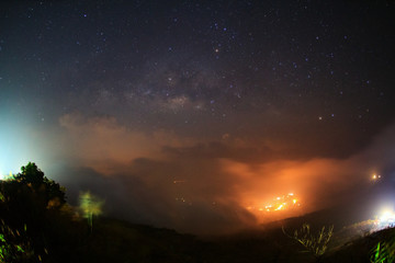 Milky way galaxy with cloud and city light at Phutabberk Phetchabun in Thailand.Long exposure photograph.With grain