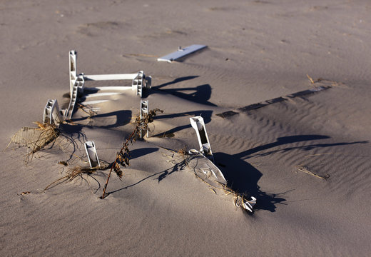 A damaged beach chair is seen buried in the sand in Atlantic Beach, New York