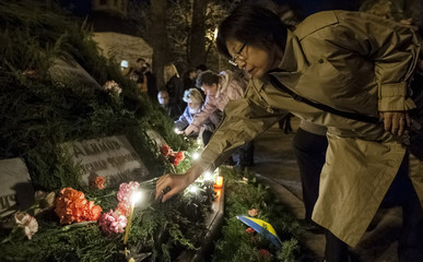 Women lay flowers and candles for victims of the Chernobyl nuclear disaster during a memorial service in Kiev