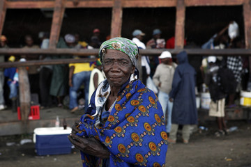 A woman working as a vendor stands in an outdoor market in the Angolan city of Lubango