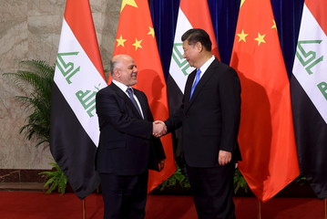 Iraqi Prime Minister Haider al-Abadi shakes hands with Chinese President Xi Jinping before their meeting at the Great Hall of the People in Beijing