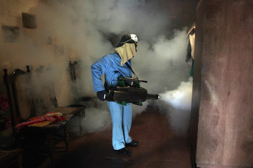 A health worker fumigates inside a home in Managua.