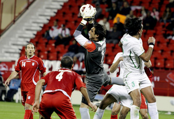 Iran's goalkeeper Mahdi Rahmati catches the ball against Iraq's Nashat Akram during their 2011 Asian Cup Group D soccer match at Al Rayyan stadium in Doha