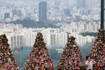 "A tourist poses for photographs in front of trees covered with ""love locks"" as an apartment complex is seen in the background in Seoul"