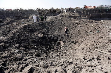 Afghan officials investigate at the site of a truck bomb attack in Kabul