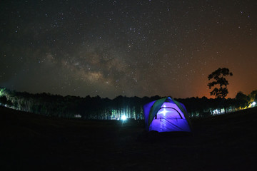 Milky Way and silhouette of tree with dome tent at Phu Hin Rong Kla National Park,Phitsanulok Thailand, Long exposure photograph.with grain