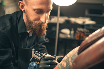 Serene bearded man making tattoo