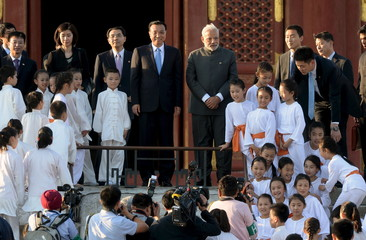 Modi and Li pose for pictures with performers at the Temple of Heaven park in Beijing