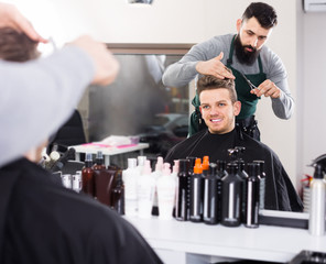 guy stylist creating haircut for man client at hairdressing salon