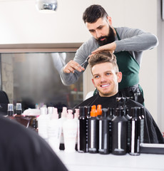 Young guy stylist creating haircut for smiling man client at hairdressing salon