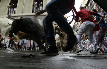 Runners sprint alongside Miura fighting bulls at the Estafeta corner on the the second day of the running of the bulls in Pamplona