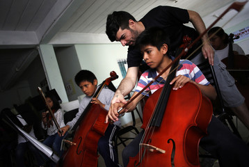 """Cellist Jorge Ramos gives instructions to children during a practice session for the """"Despertando Suenos"""" (Waking Dreams) string orchestra in the Villa Soldati slum in Buenos Aires"""