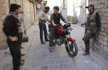 A Free Syrian Army fighter on a motorcycle chats with men in the old city of Aleppo