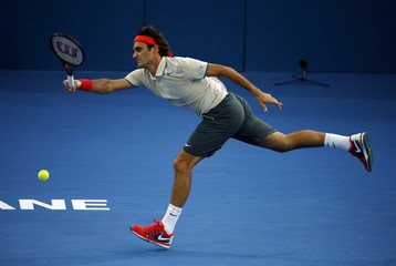 Roger Federer of Switzerland lunges for the ball against Lleyton Hewitt of Australia during their men's final match at the Brisbane International tennis tournament