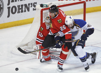 Blackhawks' Handzus and Blues' Backes race to the puck during their NHL hockey game in St. Louis