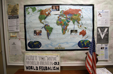 "A sign sits below a map of the world at a ""Food for Free Minds Tea Party Rally"" in Littleton"