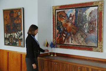 "Embassy intern poses with the artworks ""Man on a Bull"" and ""Odalisque of the Grand Canal"" by artist Theo Tobiasse at the Embassy of Lithuania in London"