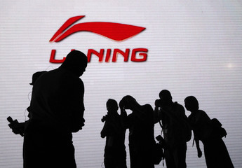 Journalists take pictures of NBA Miami Heat's Wade in front of a electronic screen showing the company logo of Li Ning during a promotional event for Li Ning's Way of Wade sneakers