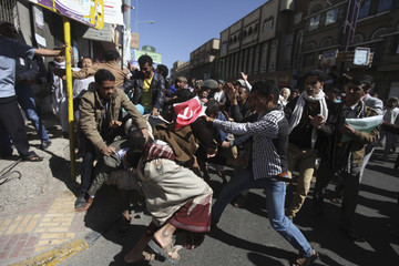 Supporters of the Houthi movement clash with anti-Houthi protesters during a rally in Sanaa